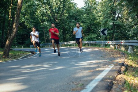 Photo for Three professional male athletes running fast in park - Royalty Free Image