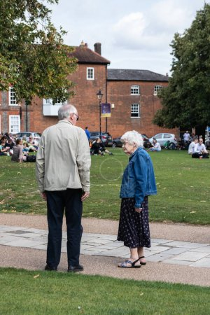 Photo for An elderly man and woman standing in a park talking - Royalty Free Image