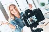 smiling young woman in casual wear smiling recording video on camera