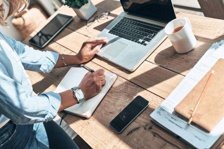 Photo pour Femme d'affaires, idées d'écriture dans un journal pour manuels à table avec ordinateur portable - image libre de droit