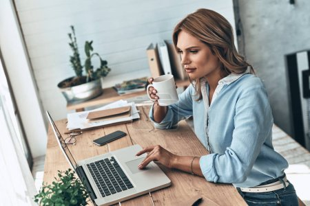 blonde woman using laptop and holding tea cup