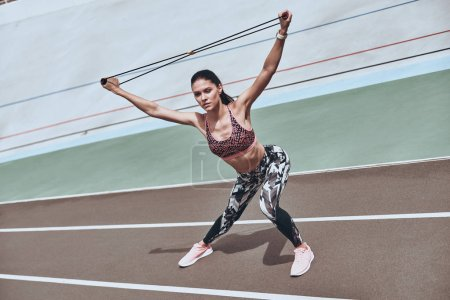 Photo for Woman in sports clothing exercising with resistance band on running track stadium - Royalty Free Image