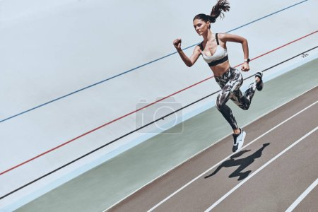 Photo for Sportive woman in sports clothing jogging on stadium - Royalty Free Image