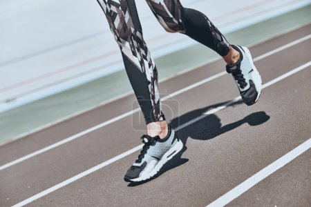 Photo for Partial view of female legs jogging on running track stadium - Royalty Free Image