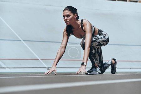 sportive beautiful woman standing on start line on running track stadium, ready to run