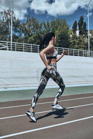 full length of brunette woman in sports clothing running on track stadium