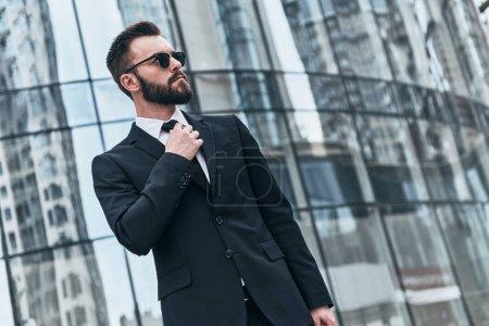 Photo pour Homme d'affaires confiant ajuster cravate tout en se tenant à l'extérieur au bâtiment de verre de bureau - image libre de droit