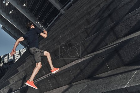 full length of man in sports clothing running on stairs in street