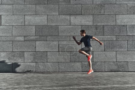 handsome young man in sports clothing jumping in city street at stone wall