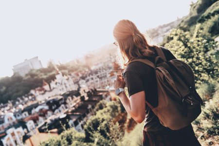 Photo for Back view of traveler man with backpack looking at city building from hill - Royalty Free Image