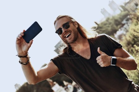 young man in casual clothing gesturing thumbs up and smiling while taking selfie outdoors