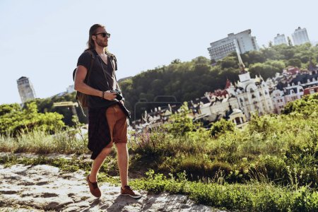 Photo pour Pleine longueur de jeune homme en vêtements décontractés marchant sur la colline à l'extérieur - image libre de droit