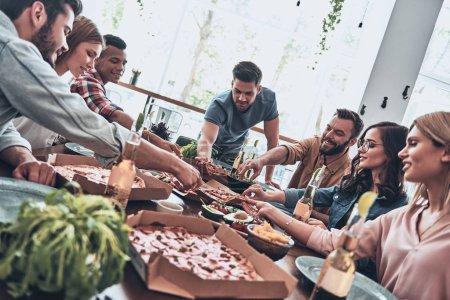 les jeunes en tenue décontractée mangeant et souriant lors d'un dîner