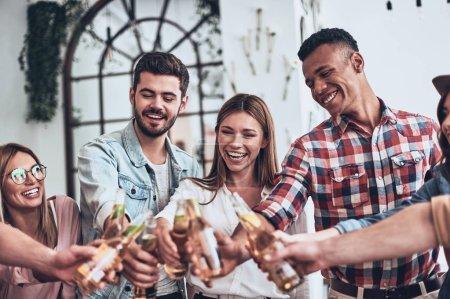 Foto de Elegantes amigos brindando entre sí con botellas de cerveza mientras tienen fiesta en el interior - Imagen libre de derechos
