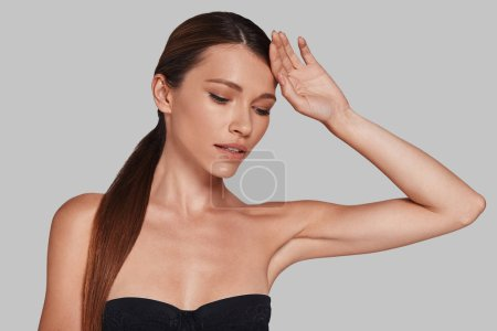 Calm and beautiful young woman keeping hand on head while standing against grey background