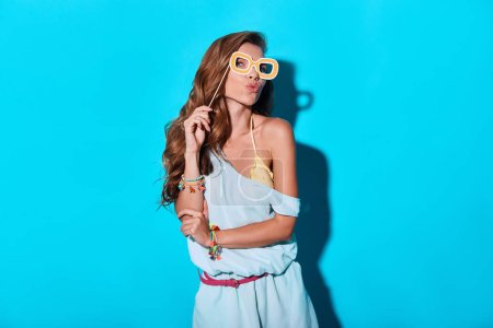Photo for Beautiful woman kissing and holding prop while standing against blue background - Royalty Free Image