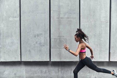 Photo pour Jeune femme sportive en vêtements de sport courir et faire de l'exercice à l'extérieur - image libre de droit