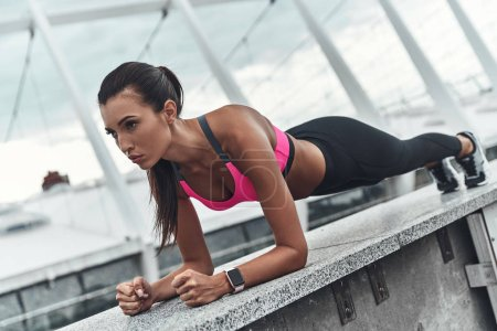 sportive woman keeping plank position, abdominal exercise