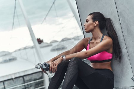 woman in sports clothing resting on roof of building and holding bottle with water