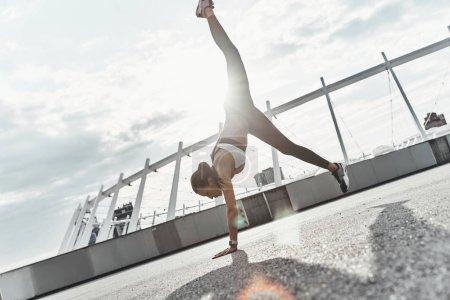 Photo pour Toute la longueur du moderne jeune femme dans le sport vêtements faisant appui renversé pendant l'exercice en plein air - image libre de droit