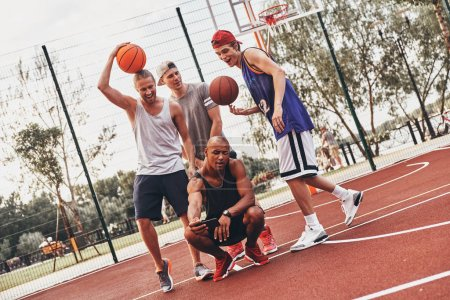 group of young men in sports clothing taking selfie on mobile phone while posing on basketball arena court