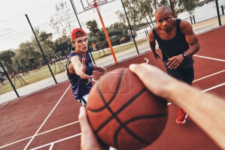 close up of man holding ball while playing basketball with friends outdoors