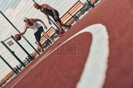 low angle view of two friends playing basketball outdoors on basketball arena court