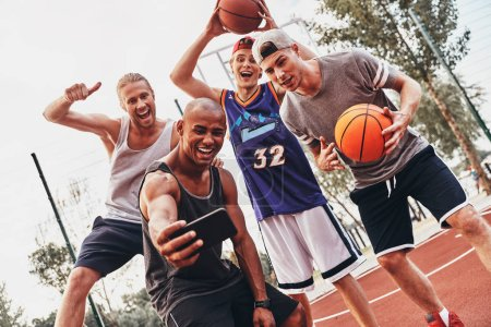 group of smiling men in sports clothing taking selfie on mobile phone while posing on basketball arena court