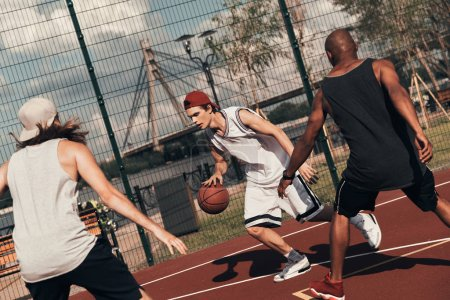 sportsmen playing basketball outdoors on basketball arena cage