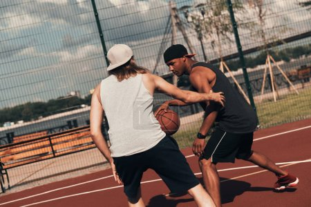 two friends playing basketball outdoors on basketball arena court