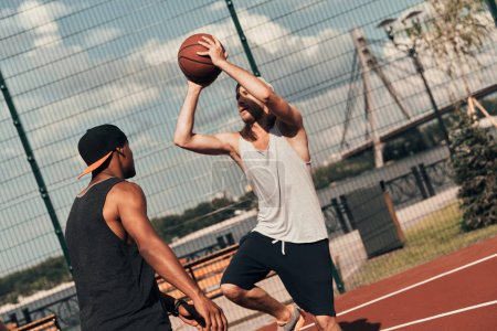 men in sports clothing playing basketball on court