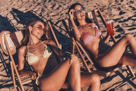 Foto de Atractivas mujeres jóvenes sonrientes y tomar el sol mientras descansa en la playa sillas con fría bebida refrescante - Imagen libre de derechos
