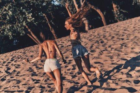 Foto de Dos mujeres jóvenes en pantalones cortos corriendo en la playa - Imagen libre de derechos