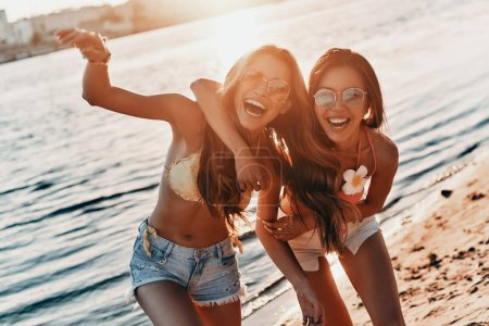 happy young women spending carefree time on beach with river and sunset