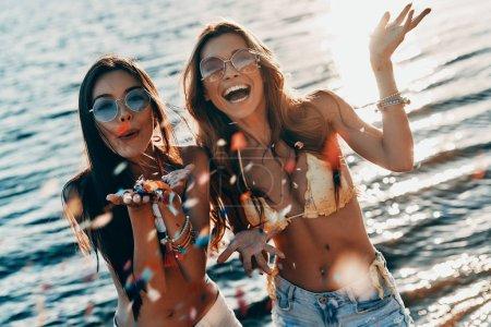 Foto de Hermosas mujeres en traje de baño sonriendo y soplando confetti estando en río en la playa de fiesta - Imagen libre de derechos