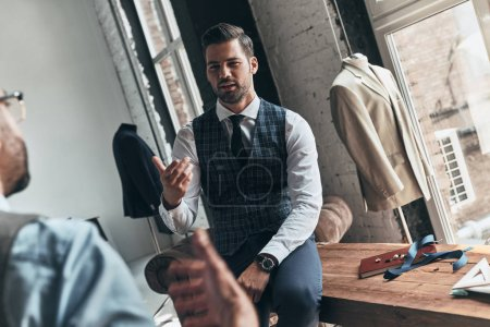 Photo for Two young fashionable men having discussion in workshop - Royalty Free Image