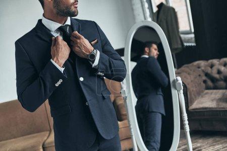 Foto de Hombre macho guapo en traje de pie en el espejo en el taller - Imagen libre de derechos