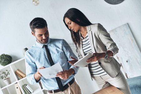 Photo for Two young colleagues discussing business while standing in the creative office - Royalty Free Image