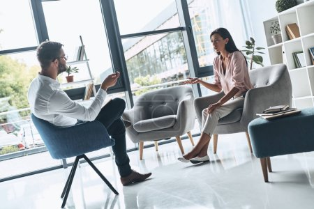 Photo for Upset woman talking to psychologist man in modern office with glass window - Royalty Free Image