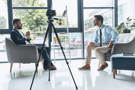man having therapy session with psychologist in modern studio with recording camera on tripod