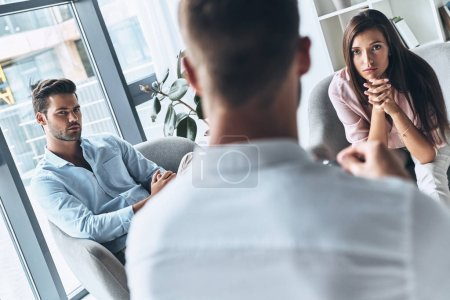 Young married couple looking at psychologist while sitting on therapy session