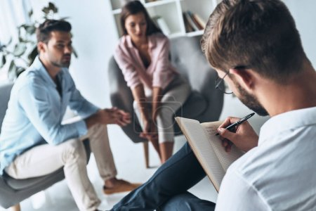 psychologist writing notes in diary, married couple sitting on therapy session