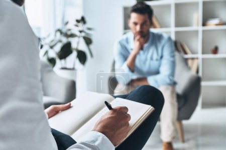 Photo for Man having therapy session with psychologist, partial view of doctor writing notes in diary - Royalty Free Image