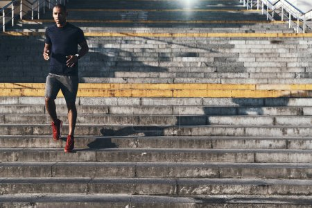young African man in sports clothing running down city stairs and looking at camera