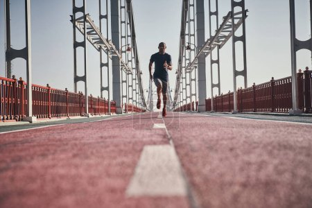 full length of sportive man jogging on bridge outdoors, low angle view