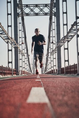 African man in sports clothing exercising and jogging on bridge outdoors