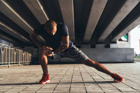 African man in sports clothing stretching legs while warming up under the bridge
