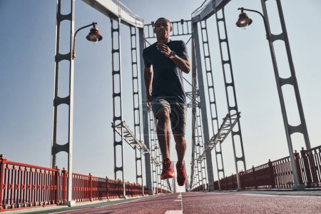 African man in sports clothing exercising and jogging on bridge outdoors, low angle view