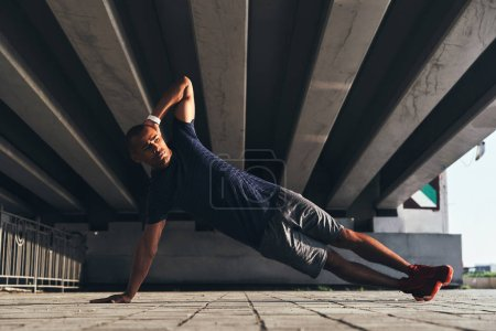 handsome young African man in sports clothing keeping plank position while warming up under the bridge
