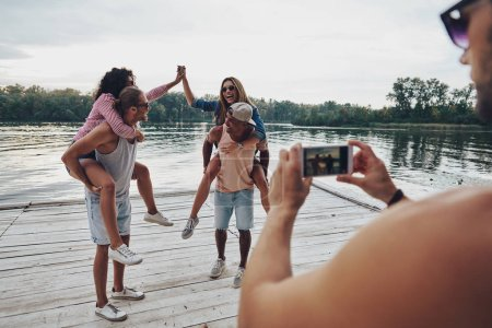 beautiful young couples spending carefree time while standing on pier, man taking mobile photo of friends having fun with piggyback